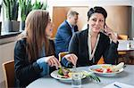 Mid adult businesswoman on call with female colleague having lunch at restaurant Stock Photo - Premium Royalty-Free, Artist: David & Micha Sheldon, Code: 698-06615547