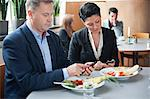 Mature businessman and female colleague using cell phones at restaurant table Stock Photo - Premium Royalty-Free, Artist: Ikonica, Code: 698-06615549