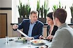 Mature businessman with colleagues discussing paperwork at restaurant table Stock Photo - Premium Royalty-Free, Artist: David & Micha Sheldon, Code: 698-06615552