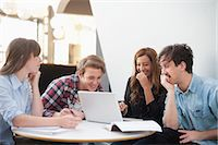 Happy college friends with laptop at restaurant Stock Photo - Premium Royalty-Freenull, Code: 698-06615593