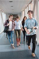 Happy young university student walking in corridor Stock Photo - Premium Royalty-Freenull, Code: 698-06615598