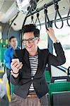 Happy mid adult businesswoman reading text message in bus Stock Photo - Premium Royalty-Free, Artist: Blend Images, Code: 698-06615636