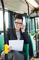 Mid adult businesswoman with document using cell phone in bus Stock Photo - Premium Royalty-Freenull, Code: 698-06615646