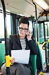 Mid adult businesswoman with document using cell phone in bus Stock Photo - Premium Royalty-Free, Artist: Blend Images, Code: 698-06615646