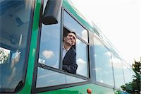 Happy mid adult bus driver looking through bus win
