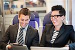 Happy businesspeople traveling in train Stock Photo - Premium Royalty-Free, Artist: Blend Images, Code: 698-06615663