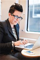 Mid adult businesswoman using laptop in train Stock Photo - Premium Royalty-Freenull, Code: 698-06615666