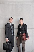 Portrait of happy business people with bags standing against wall Stock Photo - Premium Royalty-Freenull, Code: 698-06615670