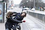 Playful young woman pushing her friend on road Stock Photo - Premium Royalty-Free, Artist: Blend Images, Code: 698-06615847
