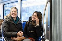 Happy female friends looking away while sitting in bus Stock Photo - Premium Royalty-Freenull, Code: 698-06615848