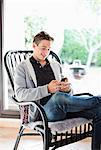 Happy young boy text messaging while relaxing on armchair at home Stock Photo - Premium Royalty-Free, Artist: Blend Images, Code: 698-06615931