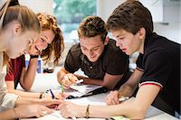 Happy young students studying together at table Stock Photo - Premium Royalty-Freenull, Code: 698-06615948