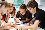 Happy young students studying together at table Stock Photo - Premium Royalty-Free, Artist: Blend Images, Code: 698-06615948