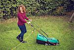 Happy young girl pushing electric lawn mower on grass Stock Photo - Premium Royalty-Freenull, Code: 698-06615954