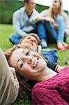 Portrait of happy young girl with head on boy's stomach and couple sitting in background at park Stock Photo - Premium Royalty-Free, Artist: Christina Krutz, Code: 698-06615975