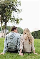 Rear view of young couple looking at each other while sitting at park Stock Photo - Premium Royalty-Freenull, Code: 698-06615977
