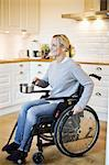 Happy disabled mid adult woman in wheelchair holding saucepan at kitchen Stock Photo - Premium Royalty-Free, Artist: Zoran Milich, Code: 698-06615990