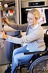 Happy disabled woman in wheelchair removing bottle from refrigerator at kitchen Stock Photo - Premium Royalty-Free, Artist: ableimages, Code: 698-06615991