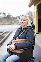 Portrait of happy disabled woman in wheelchair at railway station platform Stock Photo - Premium Royalty-Freenull, Code: 698-06616009