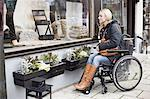 Disabled woman in wheelchair looking in store window Stock Photo - Premium Royalty-Free, Artist: Westend61, Code: 698-06616014