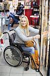 Happy disabled woman in wheelchair at refrigerated section of supermarket looking away Stock Photo - Premium Royalty-Freenull, Code: 698-06616021
