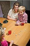 Happy family playing dice game at table Stock Photo - Premium Royalty-Free, Artist: Blend Images, Code: 698-06616023