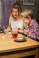 Excited boy playing dice game while mother writing scores at table Stock Photo - Premium Royalty-Freenull, Code: 698-06616025