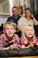 Happy little siblings watching TV with parents sitting behind Stock Photo - Premium Royalty-Freenull, Code: 698-06616032
