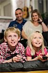 Happy little siblings watching TV with parents sitting behind Stock Photo - Premium Royalty-Free, Artist: Blend Images, Code: 698-06616032
