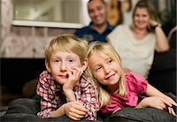 Portrait of little boy lying on front with sister watching TV Stock Photo - Premium Royalty-Freenull, Code: 698-06616035
