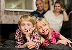 Portrait of little boy lying on front with sister watching TV Stock Photo - Premium Royalty-Free, Artist: Blend Images, Code: 698-06616035