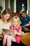 Happy girl using digital tablet with mother at home Stock Photo - Premium Royalty-Free, Artist: CulturaRM, Code: 698-06616038