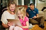 Mother and daughter using digital tablet with family in background Stock Photo - Premium Royalty-Free, Artist: Raymond Forbes, Code: 698-06616039