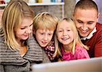 Portrait of happy girl with family using laptop at home Stock Photo - Premium Royalty-Free, Artist: Uwe Umstätter, Code: 698-06616047
