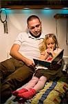 Father and daughter reading book together in bed Stock Photo - Premium Royalty-Free, Artist: CulturaRM, Code: 698-06616048