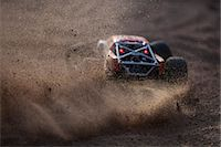 Off-road vehicle leaving a cloud of dust Stock Photo - Premium Royalty-Freenull, Code: 698-06616132