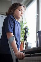Portrait of disabled girl with crutches standing by window Stock Photo - Premium Royalty-Freenull, Code: 698-06616141