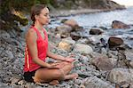 Young woman meditating on rocks at beach