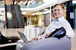 Happy senior man sitting on sofa with laptop at shopping mall Stock Photo - Premium Royalty-Free, Artist: Blend Images, Code: 698-06616191