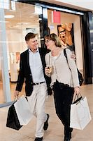 people on mall - Happy senior couple with shopping bags walking by store in mall Stock Photo - Premium Royalty-Freenull, Code: 698-06616199