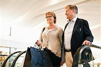 Happy senior couple with bags on an escalator in shopping mall Stock Photo - Premium Royalty-Freenull, Code: 698-06616207