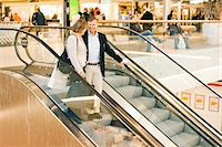 Happy senior couple on an escalator in shopping mall Stock Photo - Premium Royalty-Freenull, Code: 698-06616208