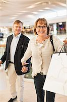 Excited senior woman pulling man in shopping mall Stock Photo - Premium Royalty-Freenull, Code: 698-06616214