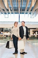 Full length of happy senior couple with bags looking at each other in shopping mall Stock Photo - Premium Royalty-Freenull, Code: 698-06616215