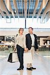 Full length of happy senior couple with bags looking at each other in shopping mall Stock Photo - Premium Royalty-Free, Artist: Blend Images, Code: 698-06616215
