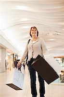 Happy senior woman carrying shopping bags in mall Stock Photo - Premium Royalty-Freenull, Code: 698-06616218