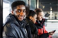 Portrait of young man smiling with friends in the background Stock Photo - Premium Royalty-Freenull, Code: 698-06616242