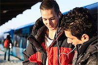 Friends using hands-free device on station Stock Photo - Premium Royalty-Freenull, Code: 698-06616248