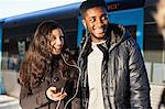 Happy young friends listening music through hands-free device against train Stock Photo - Premium Royalty-Free, Artist: Robert Harding Images, Code: 698-06616254