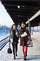 Young female friends in warm clothing walking on station platform Stock Photo - Premium Royalty-Freenull, Code: 698-06616255